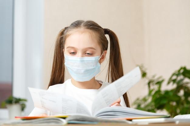 Educação à distância online. menina da escola com máscara médica faz a lição de casa em casa.