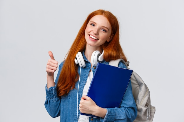 Educação, adolescentes e conceito de estilo de vida de estudante. garota adorável ruiva alegre com mochila e pasta, trazer seu portfólio para arte, classe de design, mostrando o polegar para cima em aprovação, como gesto