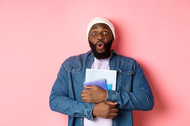 Educação. animado estudante adulto afro-americano carrega cadernos, olhando para a câmera surpreender, em pé sobre um fundo rosa.