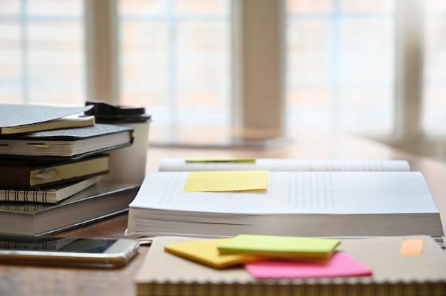 Educação, caderno, livro com lembrete na mesa de madeira.