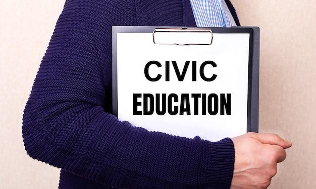 Educação cívica está escrito em um lençol branco segurado por um homem parado de lado