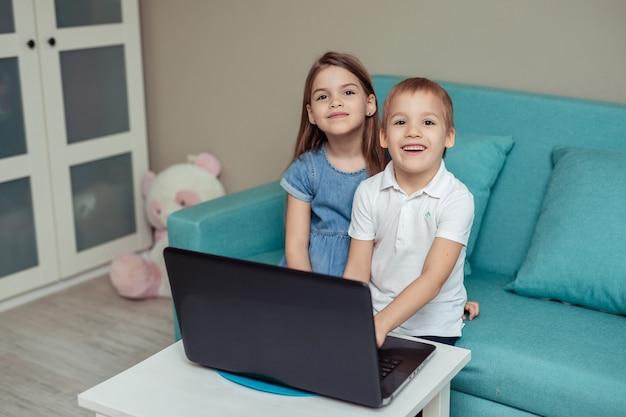 Educação domiciliar à distância de crianças em quarentena. feliz alegre gêmeo irmão e irmã, sentado no sofá e fazendo lição de casa usando laptop
