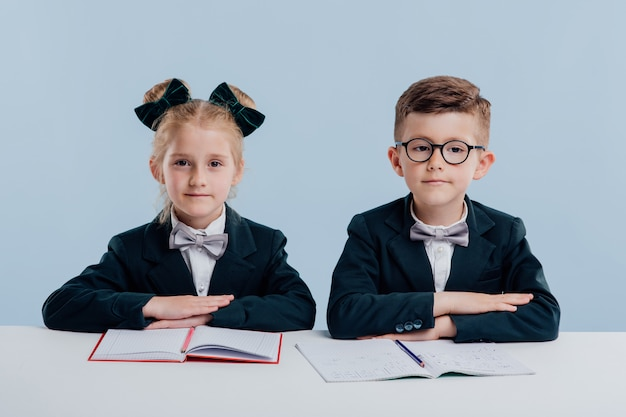 Educação. duas alunas olham para a câmera, cadernos sobre a mesa, uniforme escolar, menino e menina, sentado à mesa branca