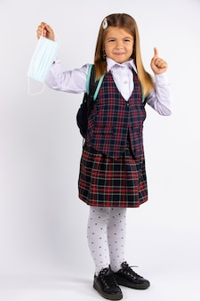 Educação durante a quarentena covid. menina criança em uniforme aponta o dedo para o lado, isolado na parede cinza.