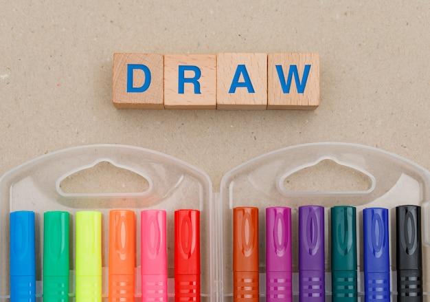 Educação e conceito de pintura com canetas de ponta de feltro, cubos de madeira em papel.