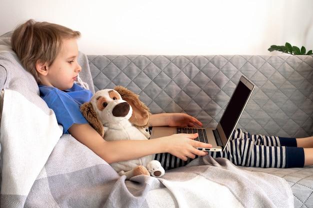 Educação e trabalho on-line a distância. criança estuda remotamente em casa, no sofá. mãos de menino segurar laptop