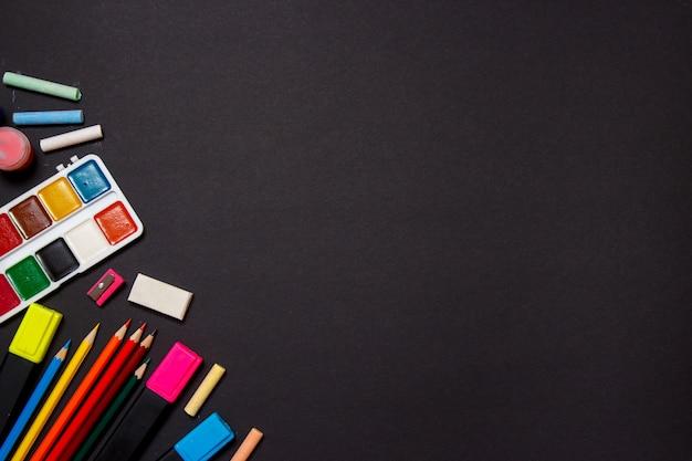 Educação e volta ao conceito de escola. material escolar para desenhar em um fundo preto. vista superior, lay plana.