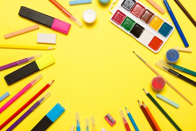 Educação e volta ao conceito de escola. material escolar para desenho sobre um fundo amarelo. vista superior, lay plana.