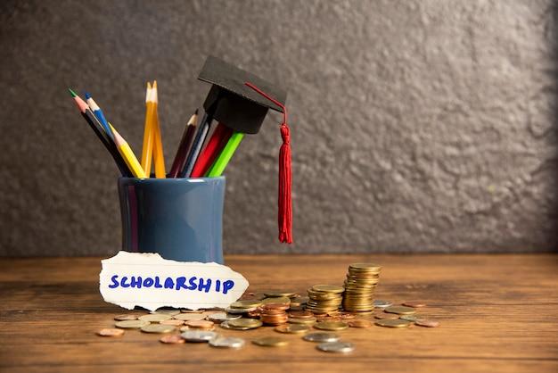 Educação e volta para a escola com chapéu de formatura na cor de lápis em uma caixa de lápis em bolsas de estudo escuras