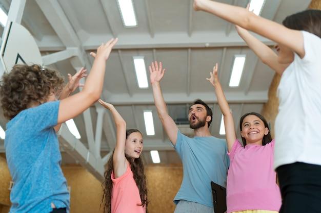 Educação física com crianças felizes e professor