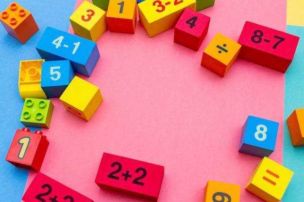 Educação infantil criança brinca cubos com padrão de matemática números no brilhante. postura plana.