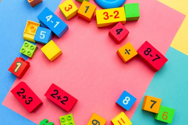 Educação infantil criança brinquedos brinquedos cubos com padrão de matemática de números. fundo brilhante. postura plana com espaço de cópia.