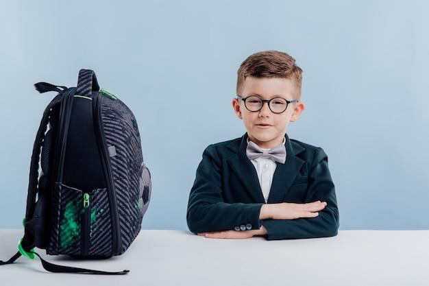 Educação. menino de uniforme escolar com mochila em cima da mesa, sentado à mesa branca