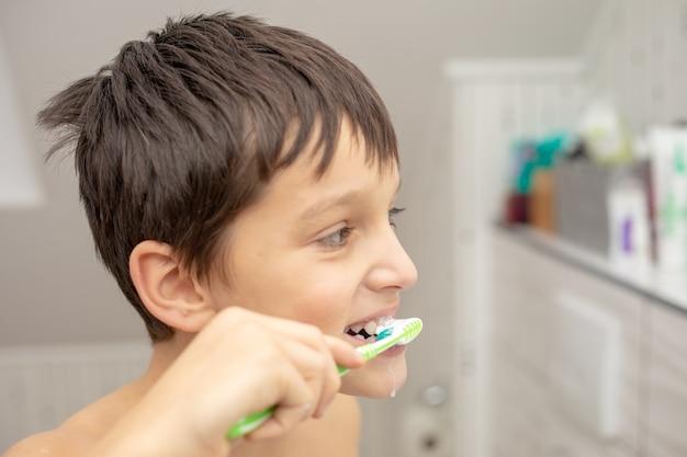Educação odontológica na família, um adolescente com alegria de 10 anos, lavando os dentes com pasta e escova de dente no banheiro