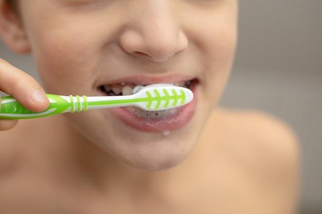Educação odontológica na família, um menino com alegria de 10 anos, lavando os dentes com pasta e escova de dente no banheiro