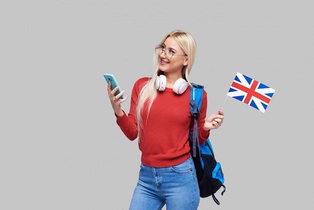 Educação on-line, tradutor de língua estrangeira, inglês, estudante - mulher loira sorridente em fones de ouvido, segurando o telefone móvel e a bandeira britânica. espaço em cinza, ensino a distância