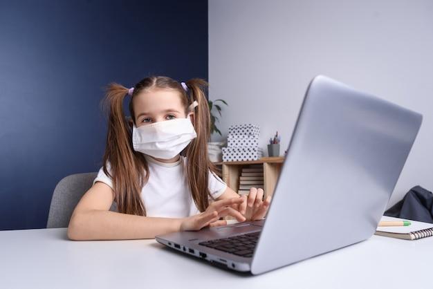 Educação online a distância. colegial na máscara médica estudando em casa, trabalhando no notebook laptop e fazendo lição de casa da escola. conceito de quarentena secreta