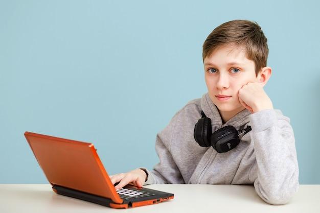 Educação online a distância. um aluno estuda em casa com um laptop digital e faz a lição de casa.