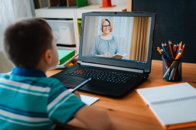 Educação online a distância. um menino estuda em casa e faz as tarefas da escola. um ensino à distância em casa