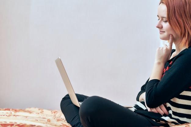 Educação online. a garota segura o laptop sentado, olha para o monitor e pensa. vista lateral. trabalhar em casa