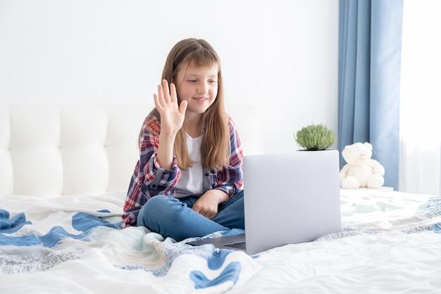 Educação online de ensino à distância. aluna estudando com laptop laptop digital e fazendo a lição de casa deitada na cama em casa