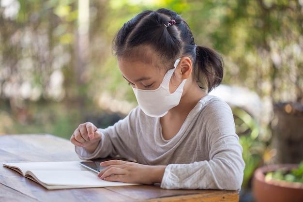 Educação online de ensino à distância. criança com uma máscara para assistir a uma aula online.
