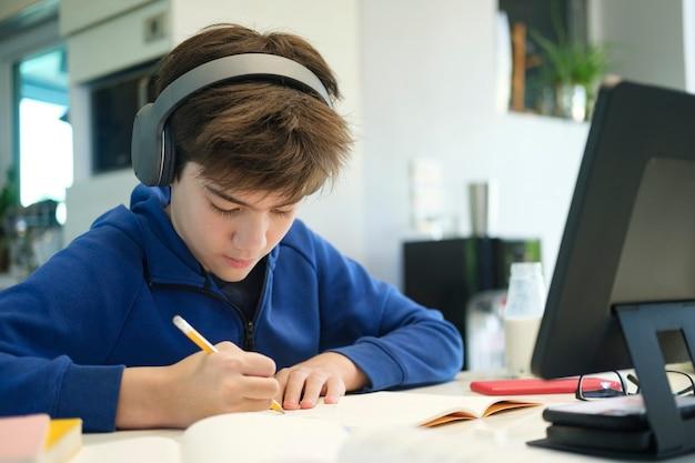 Educação online de ensino à distância. um menino de escola estuda em casa e faz os deveres escolares. um ensino à distância em casa.