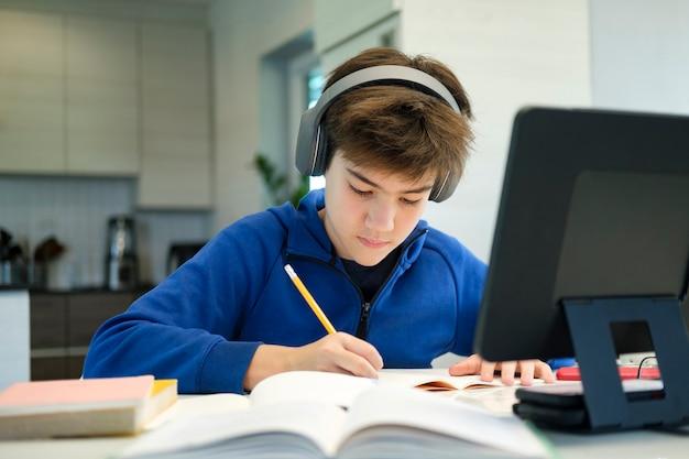 Educação online. educação online de ensino à distância. um menino de escola estuda em casa e faz os deveres escolares. um ensino à distância em casa.
