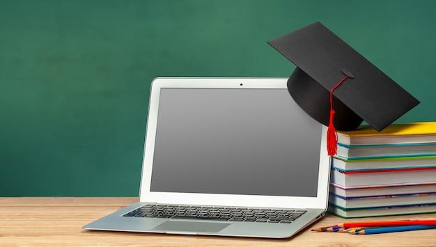 Educação online. ensino à distância em casa. laptop e pilha de livros com chapéu de pós-graduação.