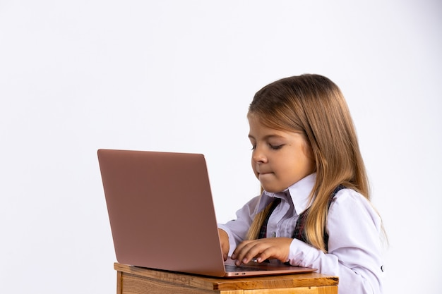 Educação online para crianças. uma estudante ensina o currículo escolar usando um laptop. foto na parede branca.