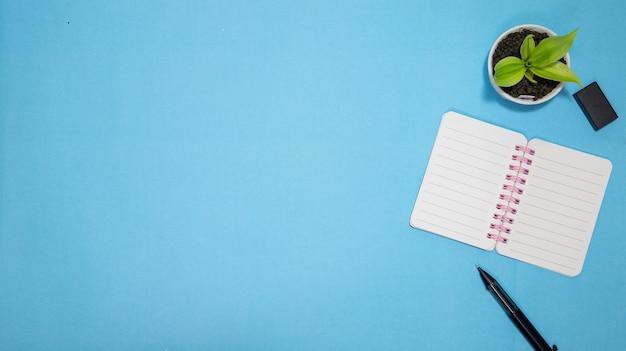 Educação ou volta ao conceito de escola. vista superior do material escolar colorido com livros, lápis de cor, calculadora, clipes de cortador de caneta e maçã sobre fundo azul pastel. postura plana.