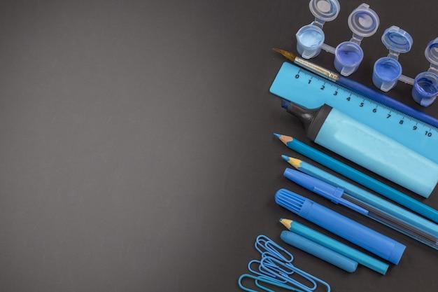 Educação ou volta às aulas. material escolar azul no quadro-negro com copyspace.