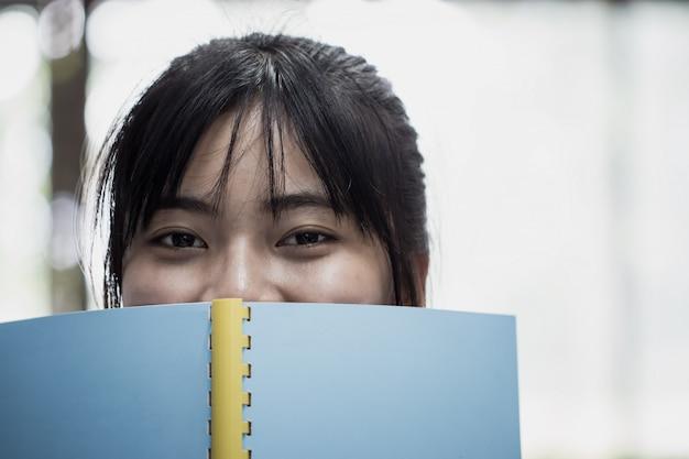 Educação para ler o livro e aprender estudar o conceito: estudante asiática olhando para a câmera