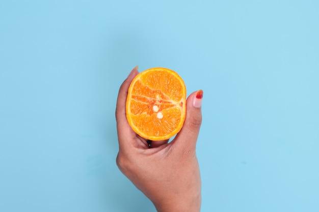 Educação sexual com laranja isolada em fundo azul