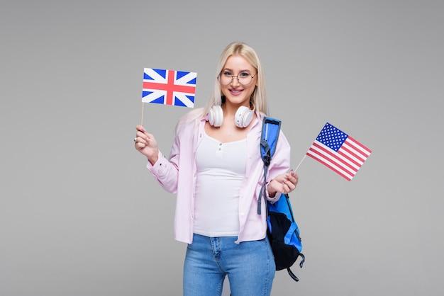 Educação, tradutor de línguas estrangeiras, inglês, estudante - mulher loira sorridente em fones de ouvido segurando bandeiras americanas e britânicas. ensino à distância