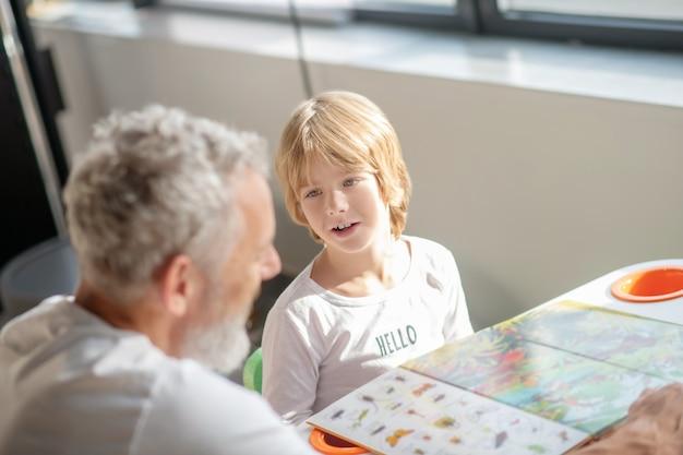Educação. um menino aprendendo espécies animais enquanto lê um livro com seu pai
