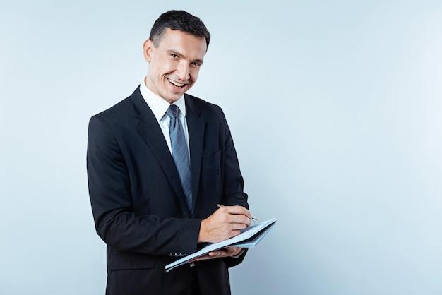 Educado e bem-sucedido. tiro da cintura para cima de um funcionário do sexo masculino alegre olhando para a câmera com um sorriso no rosto enquanto faz algumas anotações e posa.
