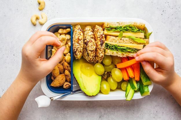 Eduque a caixa de almoço saudável com sanduíche, bolinhos, frutas e abacate no fundo branco.