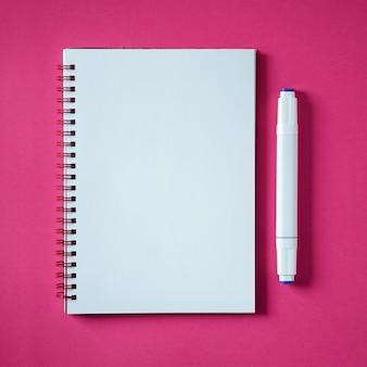 Eduque o caderno em um rosa, bloco de notas espiral em uma tabela. vista superior copie o espaço. bloco de notas de escritório plana leigos.