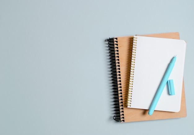 Eduque o conceito, cadernos com canetas em um fundo cinzento. de volta à escola.