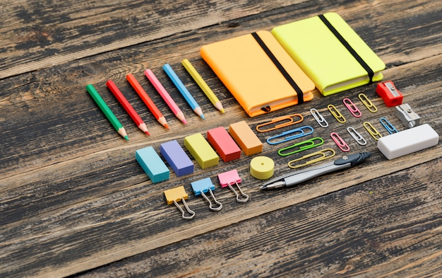 Eduque o conceito com cadernos, material escolar na opinião de ângulo alto da tabela de madeira.