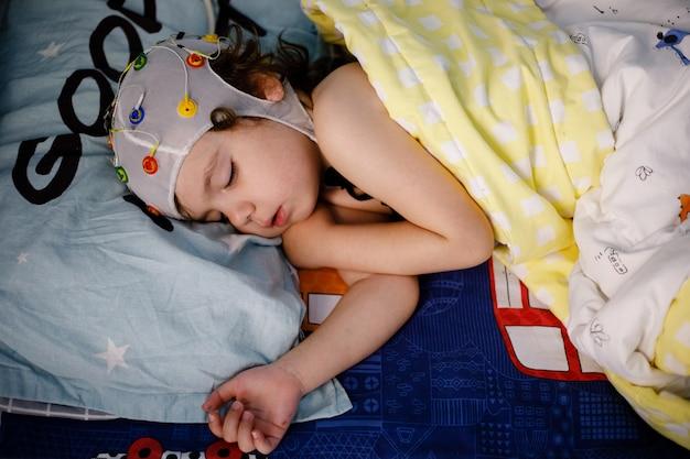 Eeg, procedimento de eletroencefalografia, encefalografia de um menino pequeno em um sonho