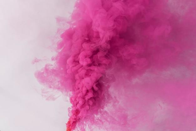 Efeito de fumaça rosa em um papel de parede branco