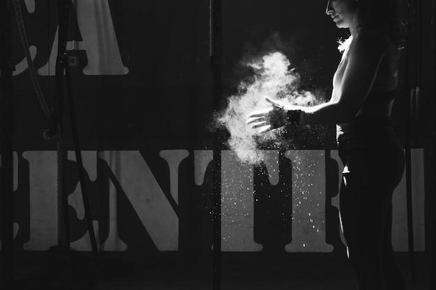 Efeito preto e branco da mulher secando as mãos com magnésio