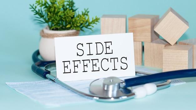 Efeitos colaterais - palavras escritas na ficha médica branca, com máscara de medicamento, estetoscópio, flor verde e blocos de madeira no fundo.