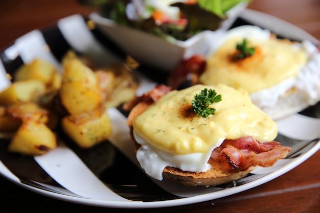 Egg benedict com bacon e batata no fundo de madeira