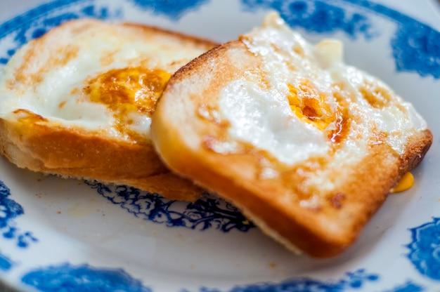 Eggy pão no prato, fotografado com luz natural. torradas francesas de ouro com manteiga e ovo. pequeno-almoço com pão. café da manhã inglês. café da manhã saudável com ovos