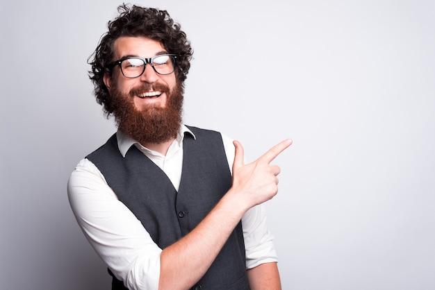 Ei, mano, olhe para esta oferta, homem barbudo hipster de terno apontando para copyspace