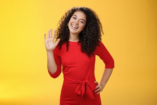 Ei, meu nome é. com aparência amigável, confiante e despreocupada, mulher bonita dos 25 anos com cabelo encaracolado acenando com a palma da mão levantada em um gesto de olá ou oi sorrindo amplamente cumprimentando novos colegas de trabalho sobre fundo amarelo.