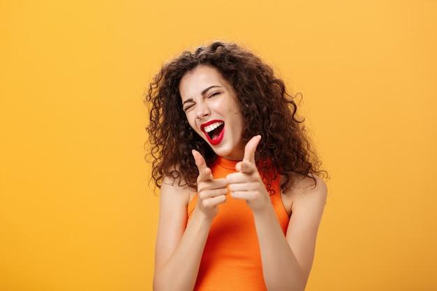 Ei, o que está acontecendo. mulher de cabelos cacheados atraente amigável e extrovertida com batom vermelho apontando para a câmera com armas de dedo como se cumprimentando ou insinuando amigo piscando para a câmera sobre fundo laranja.